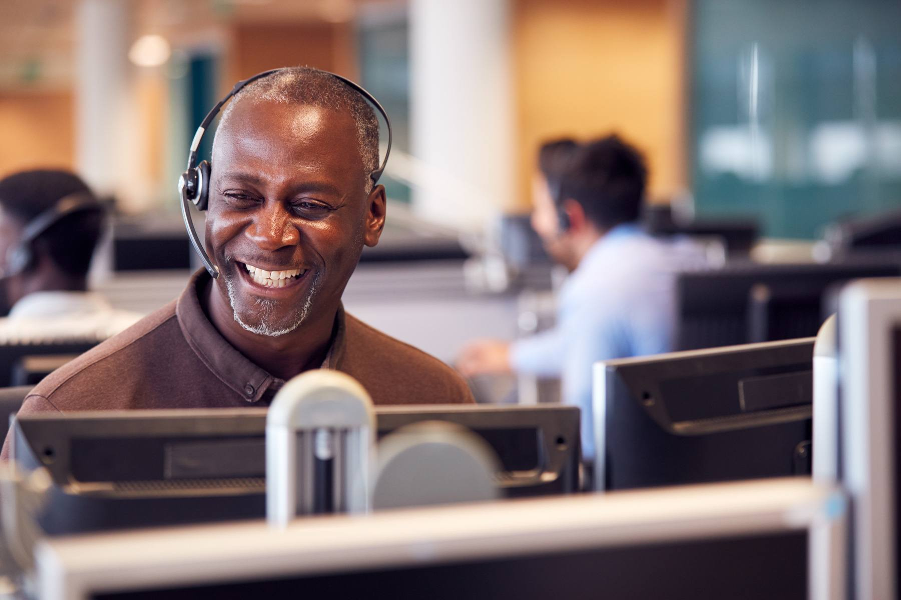 smiling man with headset in call center