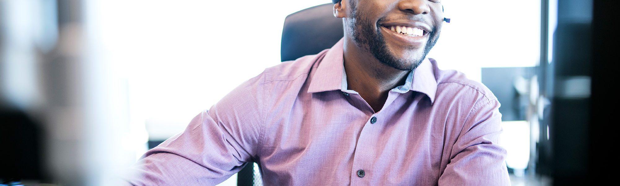 Financial - African American businessman wearing headphones looking at computer smiling